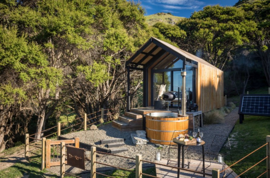 Tiny home with pitched roof, glass facade and wooden outdoor tub