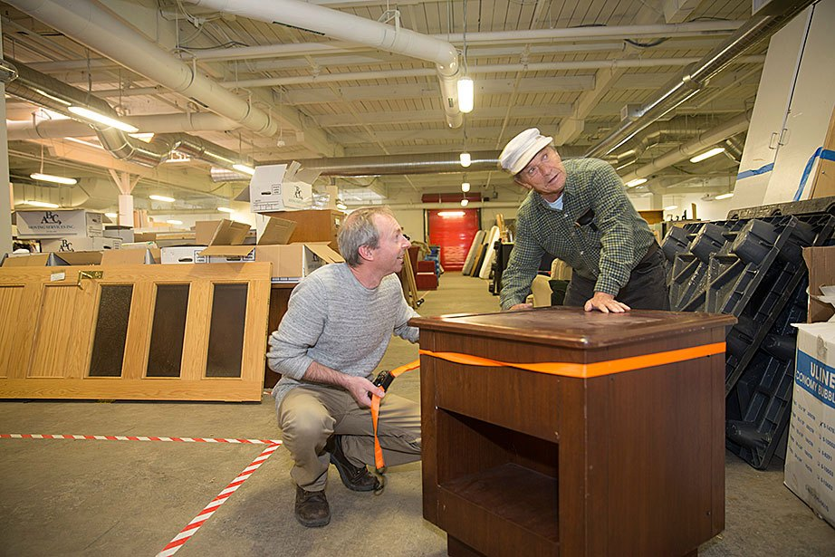 "Kieran Clyne, operations supervisor for landscape and recycling, and Franco Camporesi, volunteer and Allston resident, repair a donated table at the Harvard Recycling and Surplus Center at 156 Western Ave., Allston. The University prioritizes the reuse of furniture and other materials through donations to more than 200 local organizations, ""freecycle"" events, and by distributing surplus furniture and equipment to the community at the Recycling and Surplus Center."