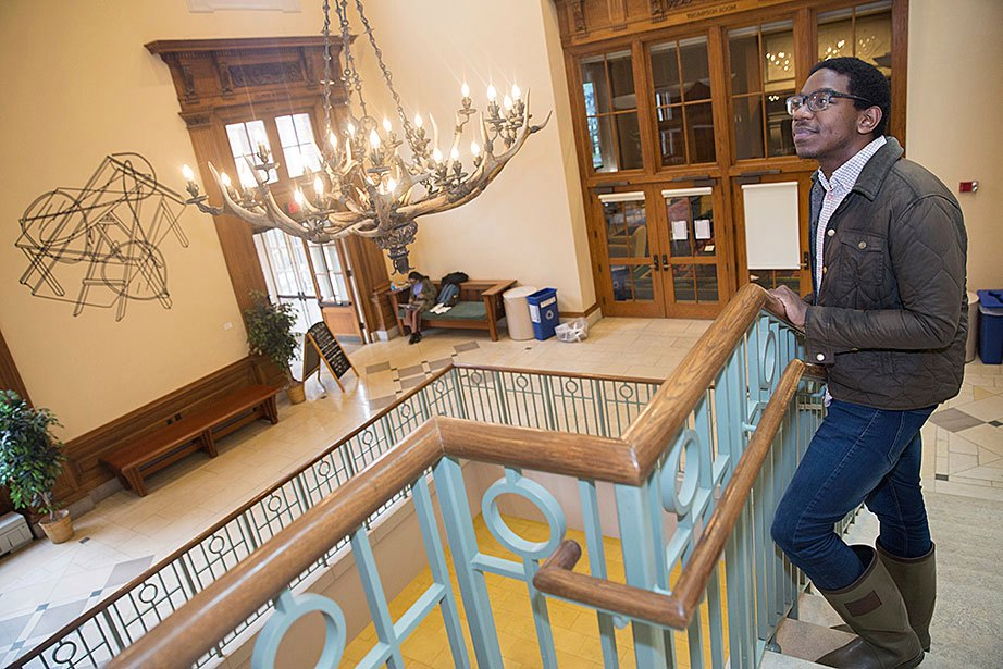 Inside the great staircase in the Barker Center, Bradley Craig, a student in the Graduate School of Arts and Sciences, marvels at the antler chandelier that was donated by President Theodore Roosevelt and recently upgraded with LED bulbs. The energy-efficient bulbs are being installed throughout the University's buildings, including the Harvard Art Museums and Widener Library, as part of Harvard's focus on improving energy efficiency and reducing greenhouse gas emissions.