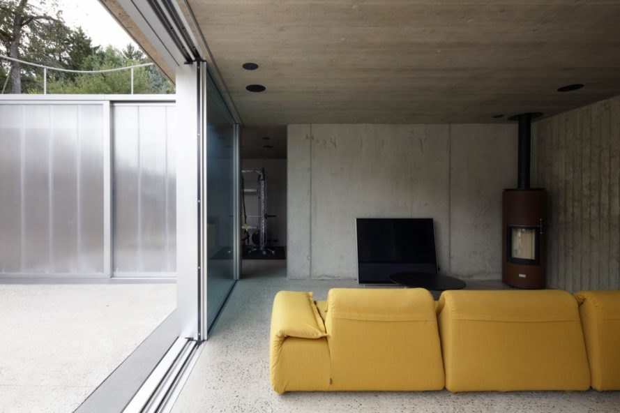 yellow couch in a gray room with a wood-burning stove