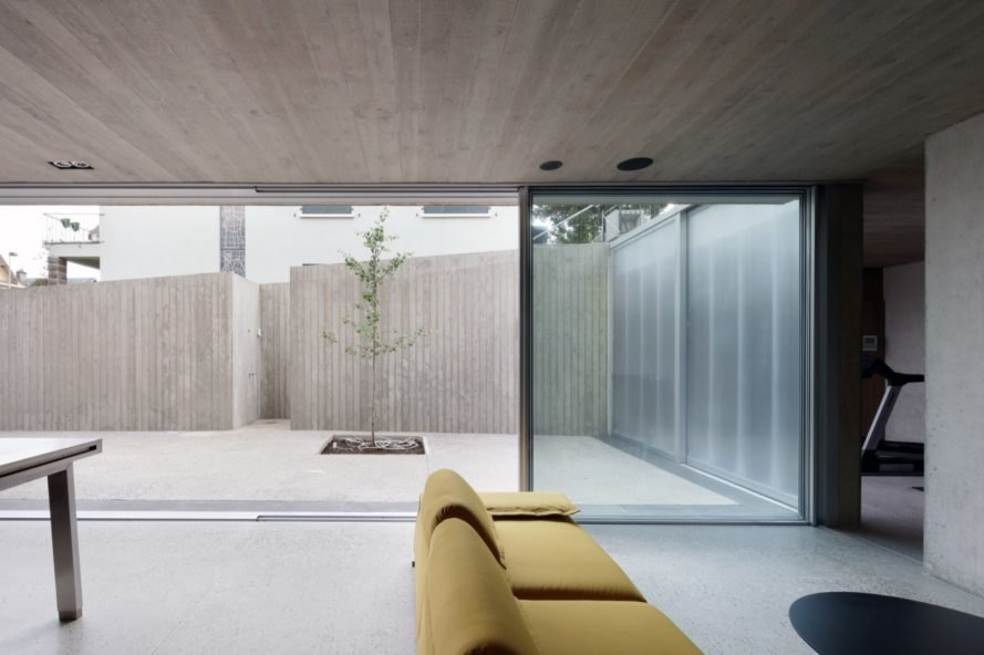 gray room with yellow couch opening to patio through sliding glass doors
