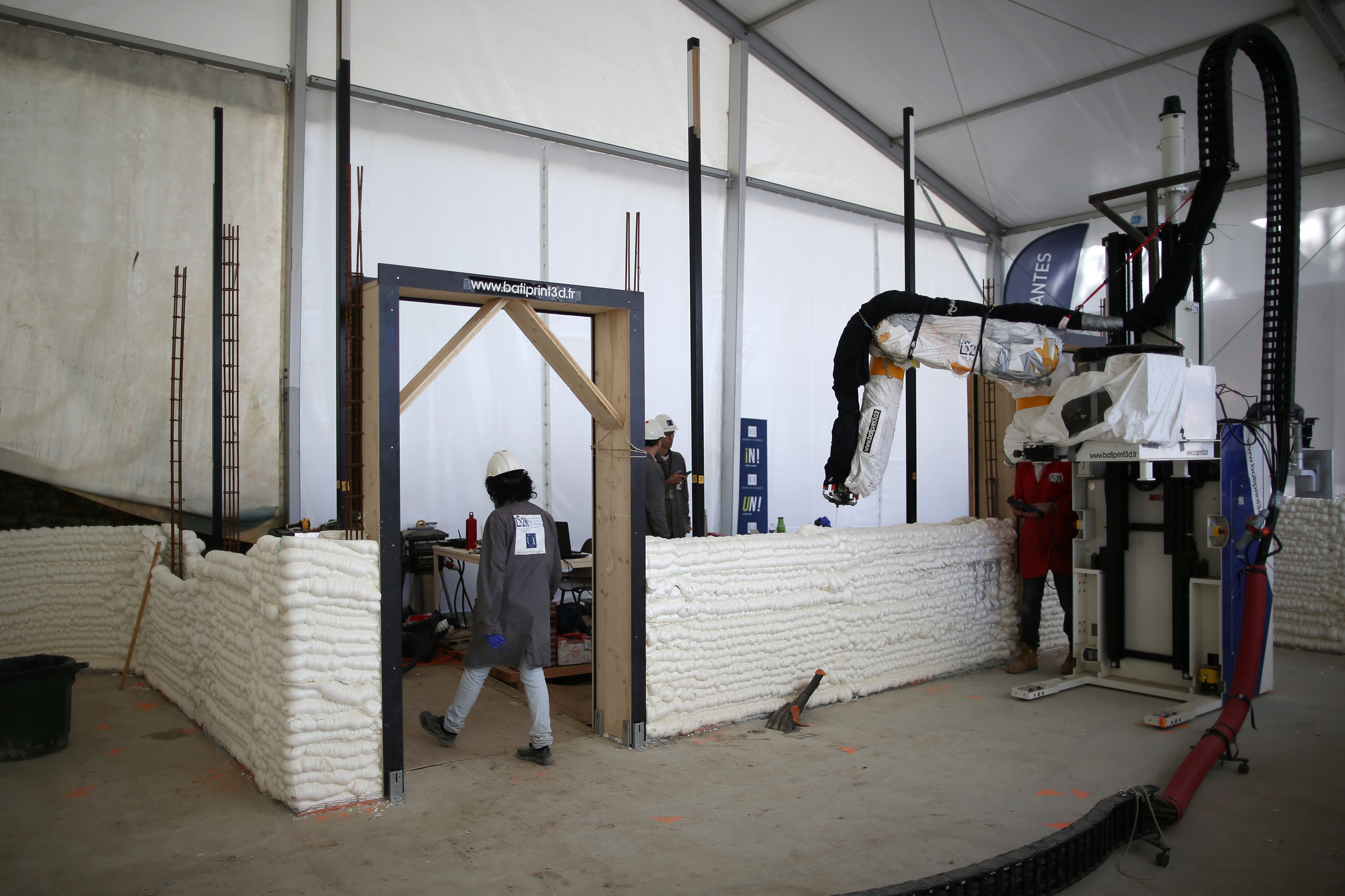 An employee works to build a 3D printed social housing building called