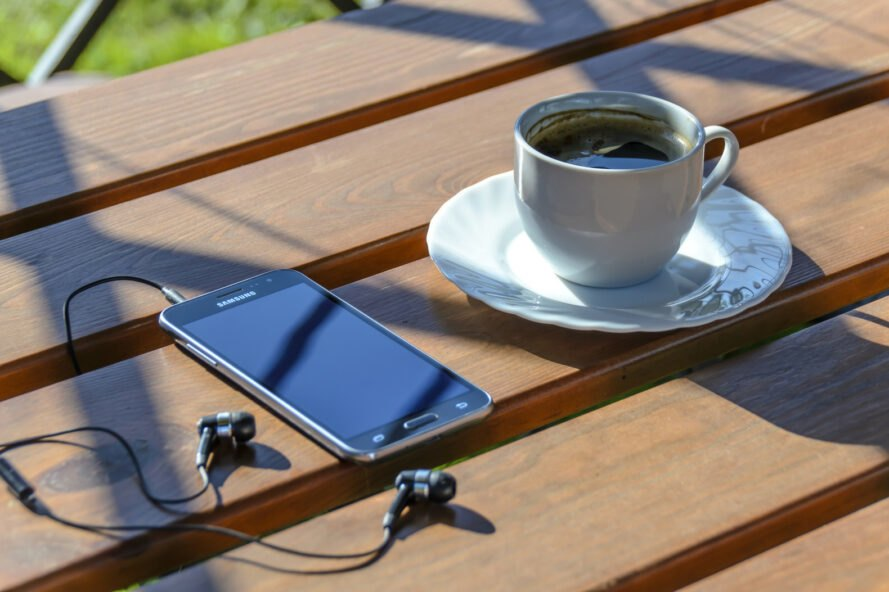 smartphone and earbuds next to cup of coffee on wood table