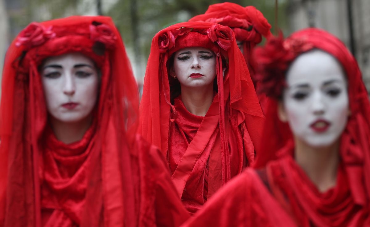 Climate change activists in red costume protest during the ongoing Extinction Rebellion climate change demonstration, near the Houses of Parliament in central London on April 23, 2019.