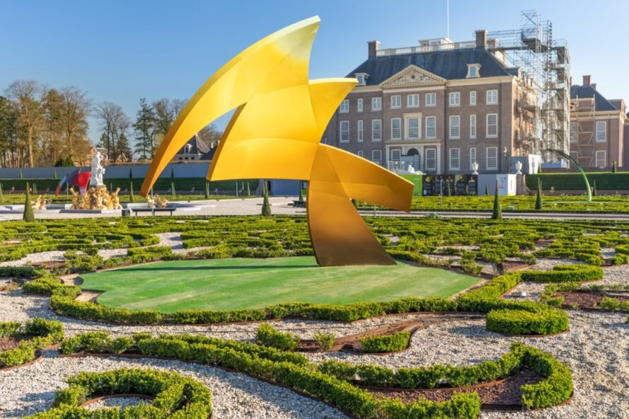yellow sculpture with jagged edges in a garden