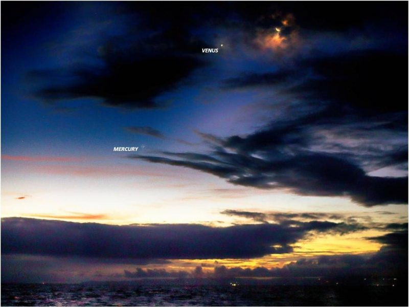 Partly cloudy dawn above the ocean, with the moon and 2 planets.