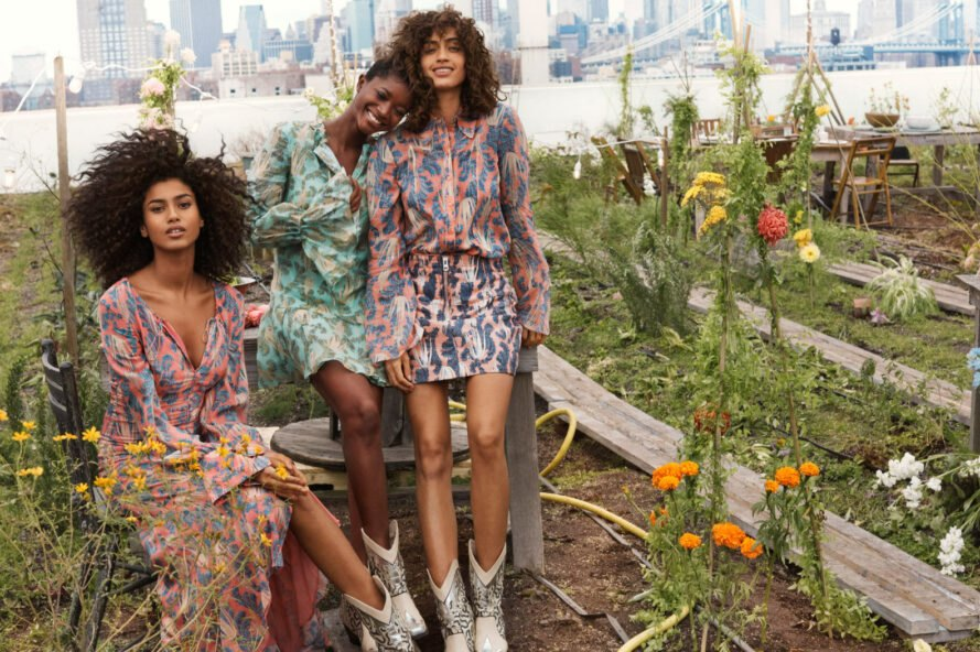 three models in dresses in a garden