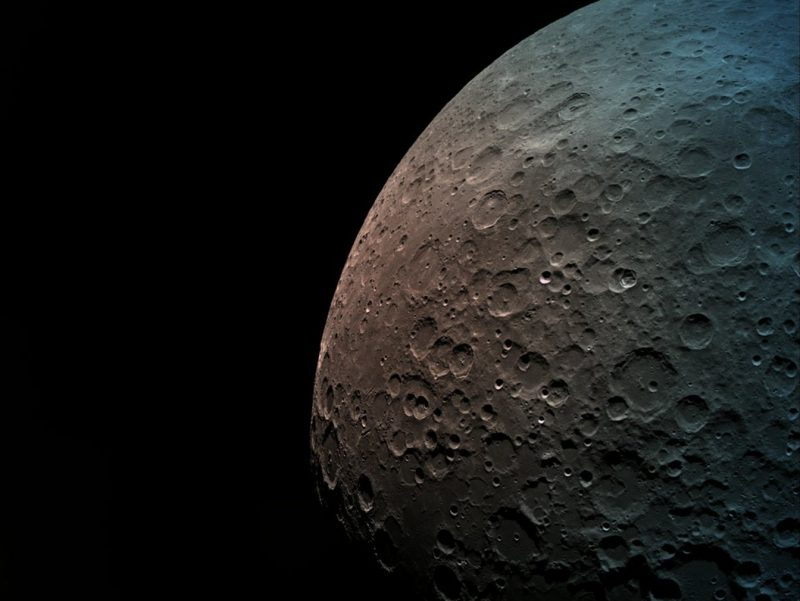 Lightly cratered surface of the moon in color, slightly brownish on horizon.