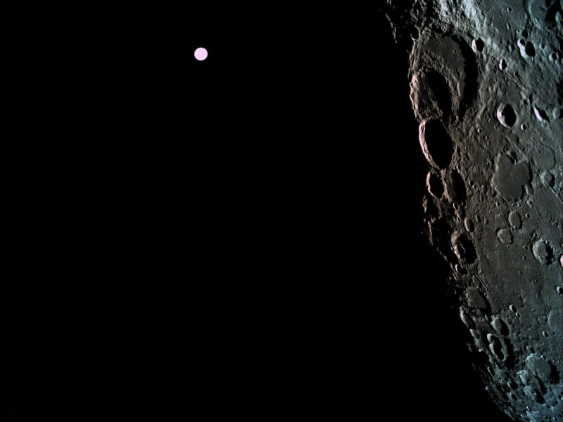 Closeup of side of moon, lots of craters, and much smaller white circle beside it.