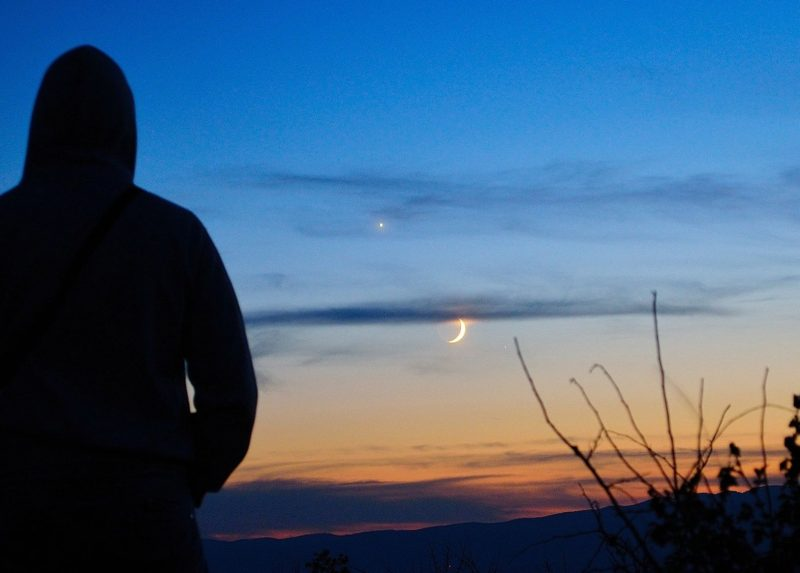 silhouette of man against the sunset sky with bright planet and crescent moon.
