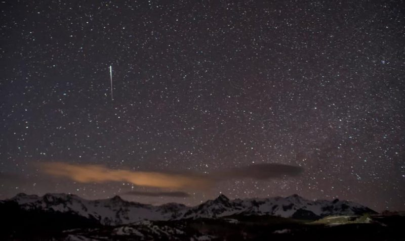 White streak in star field above mountainous horizon.