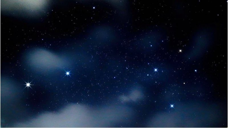 Two bright stars in a line, pointing to 4 stars in a square, in semi-cloudy sky.