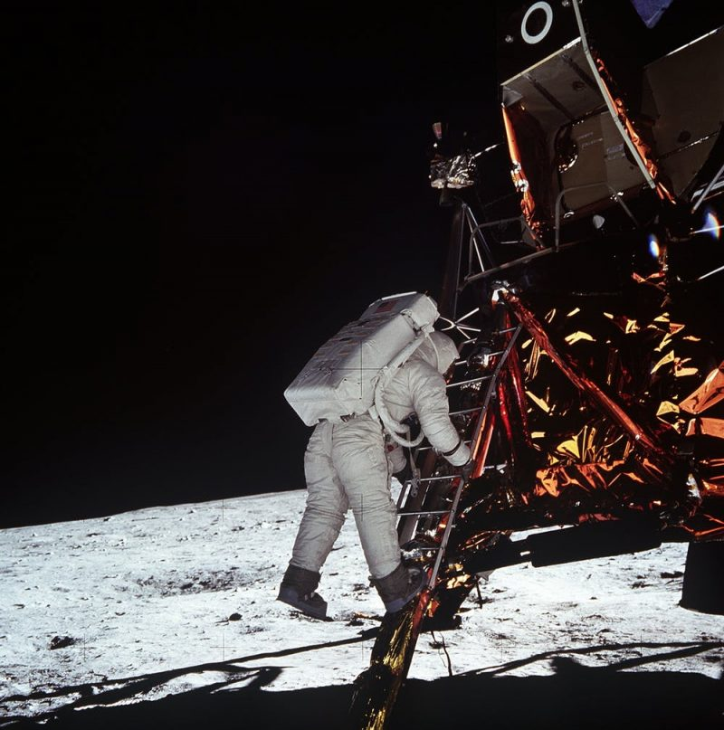 Astronaut on ladder from gold foil covered lunar module, moon horizon and black sky in background.