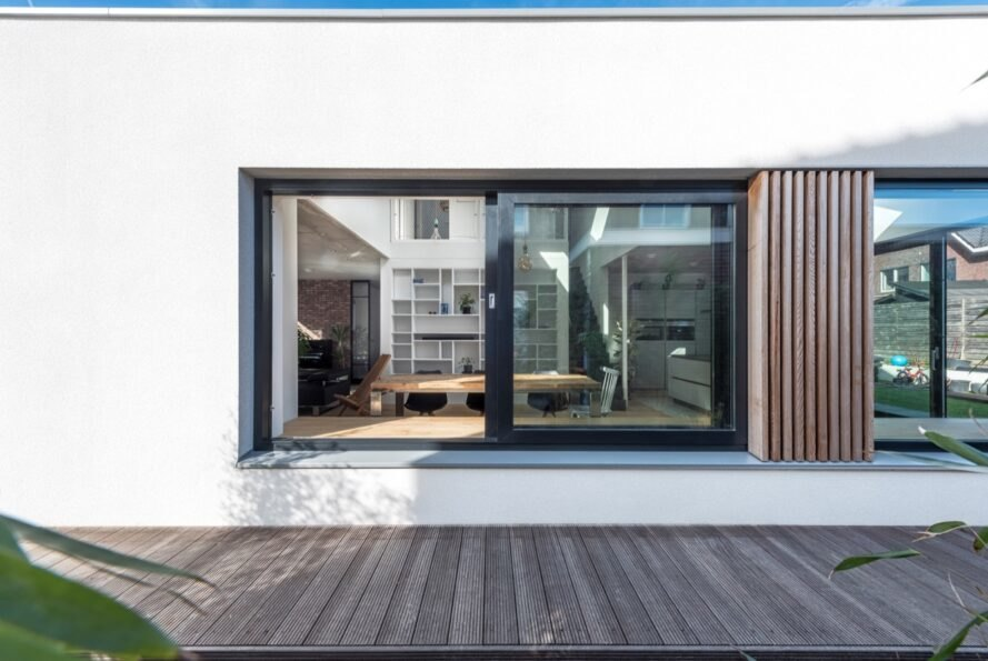 white home with large window facing the outdoor wooden deck