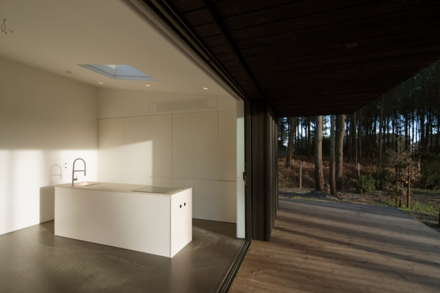 white kitchen near open wall leading to wood deck