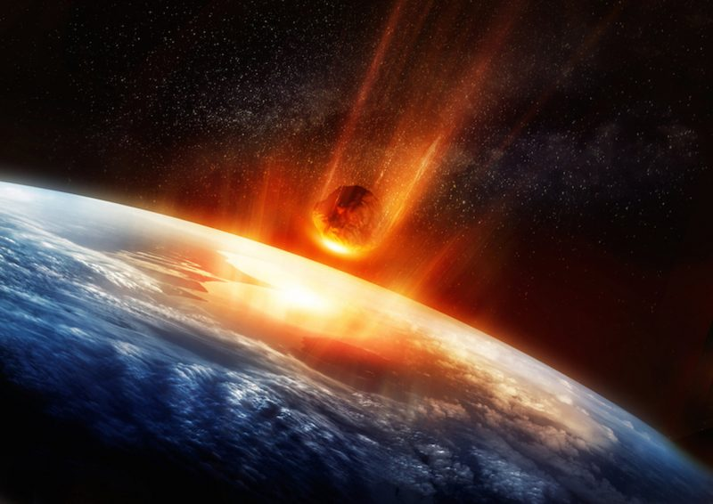 Glowing asteroid with orange tail rushing downward toward Earth.