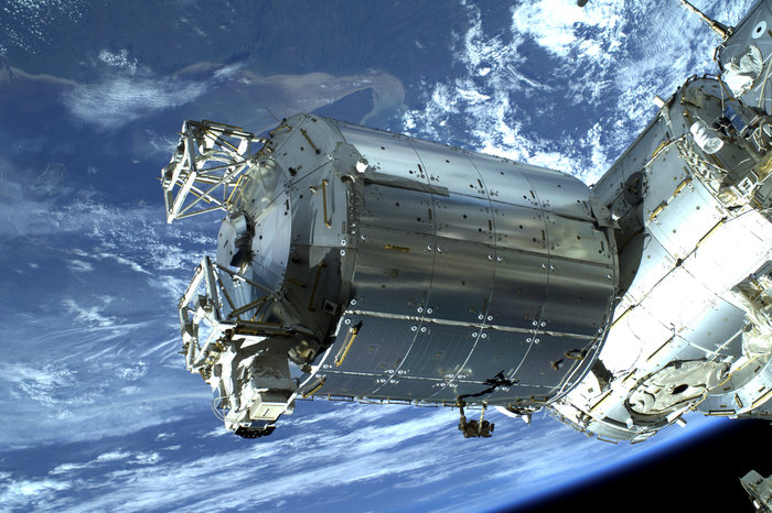 Shiny silver cylindrical spacecraft in front of blue planet Earth.