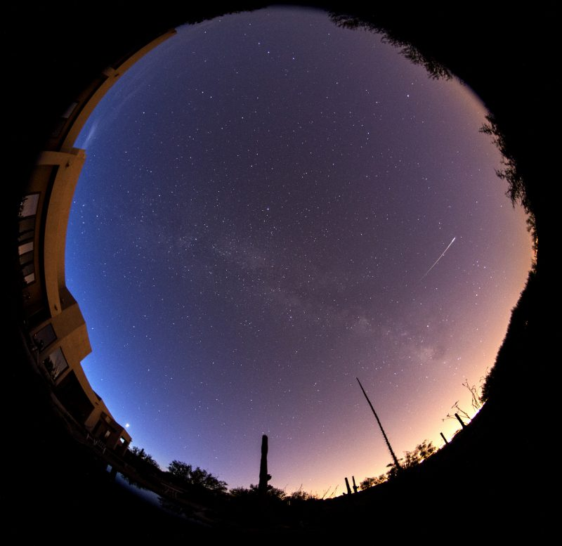 Circular panorama of whole sky, white streak with brighter end, dawn on one side of sky.