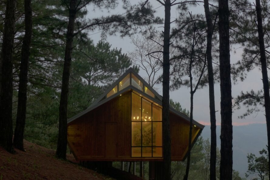 front view of a geometric wood cabin in a forest