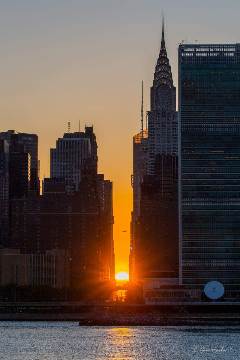 Tall buildings each side of golden sunset, half the sun above the horizon, waterway in foreground.