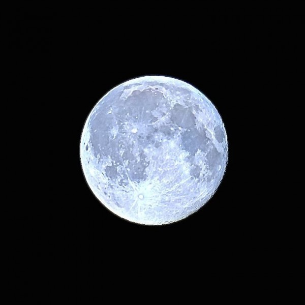 A bright, light blue-colored full moon against a black sky.