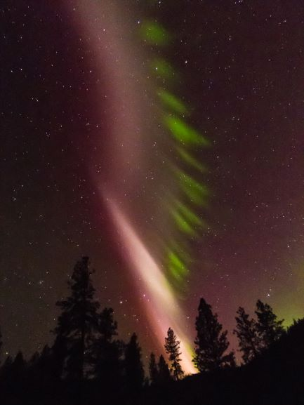 Tall twisted column of pink like beside aurora divided into horizontal pieces.