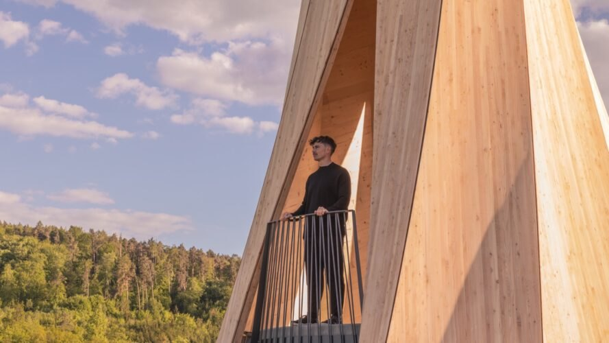 person standing on balcony of twisted wood structure