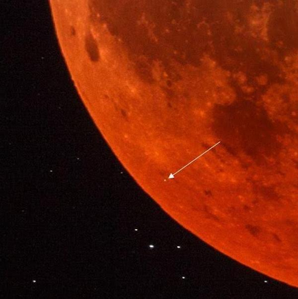 Close-up of a section of the dark orange eclipsed moon, with arrow pointing to tiny meteorite flash.
