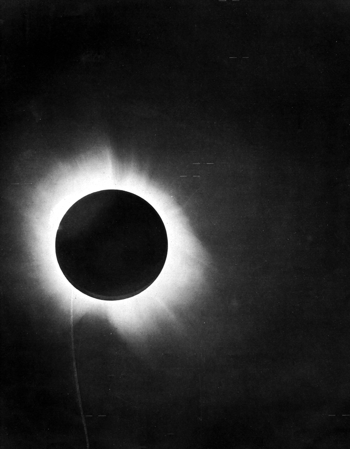 Black circular silhouette of new moon, surrounded by solar corona, during a total solar eclipse.
