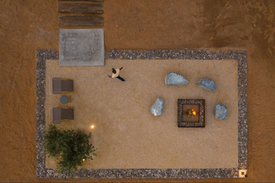 aerial shot of man walking away from fire pit