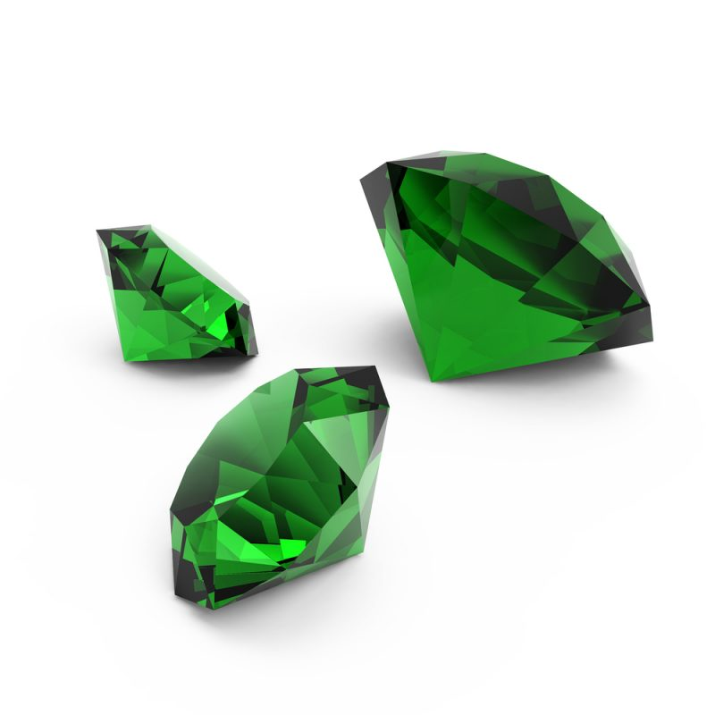 Enlarged view of three brilliant green faceted gemstones.