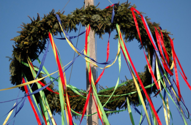 Horizontal green wreath at top of pole with brightly colored ribbons hanging off it.