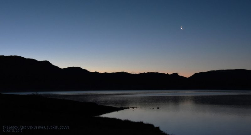 Moon and Venus at dawn over lake and silhouetted hills.