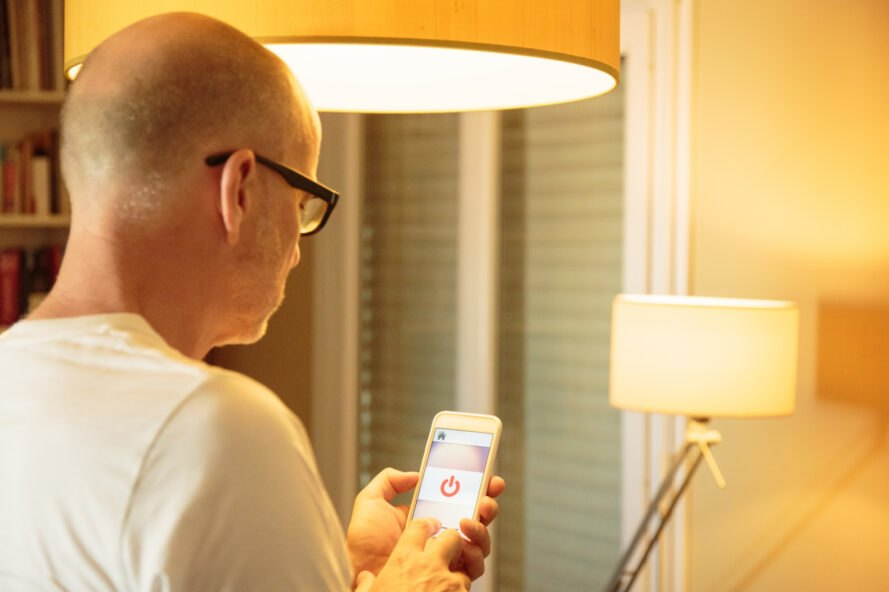 Man using smart phone to turn off lamp