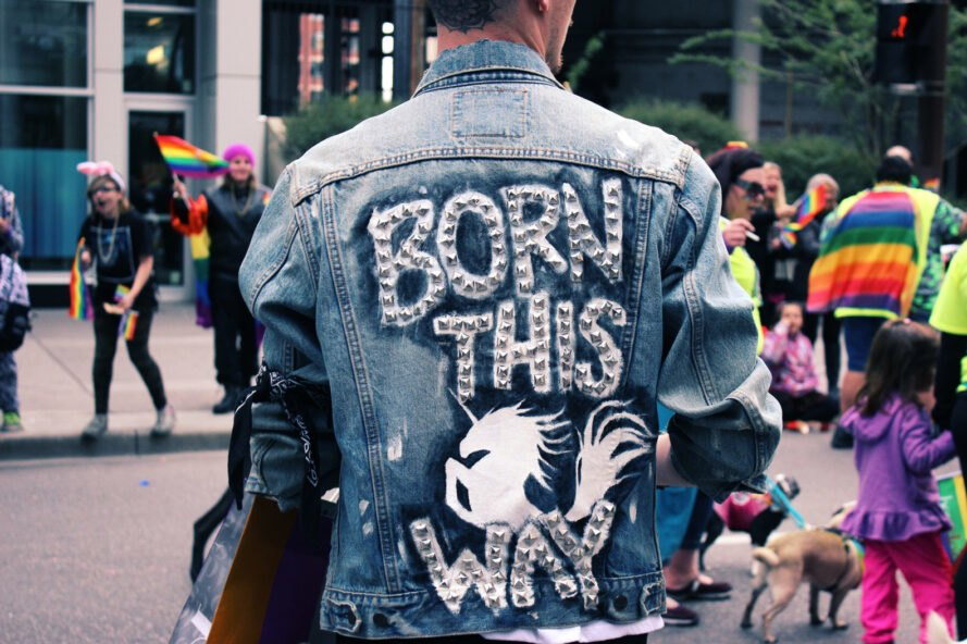 """person at Pride parade wearing DIY decorated jacket that reads """"Born This Way"""""""