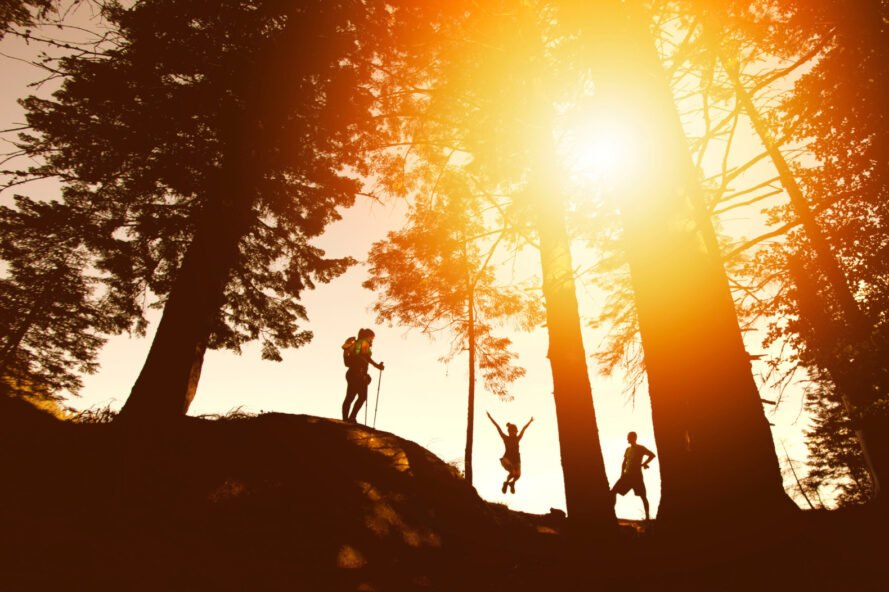 silhouettes of people hiking at sunset