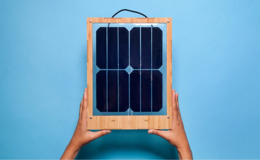 two hands holding a frame with solar panels