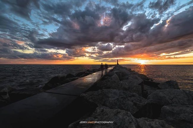Perspective view of dark clouds over bright sunset, long pier running toward horizon.