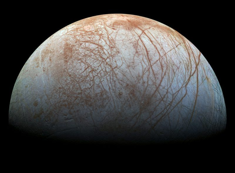 Jupiter's moon Europa showing pattern of brown lines on whitish surface.