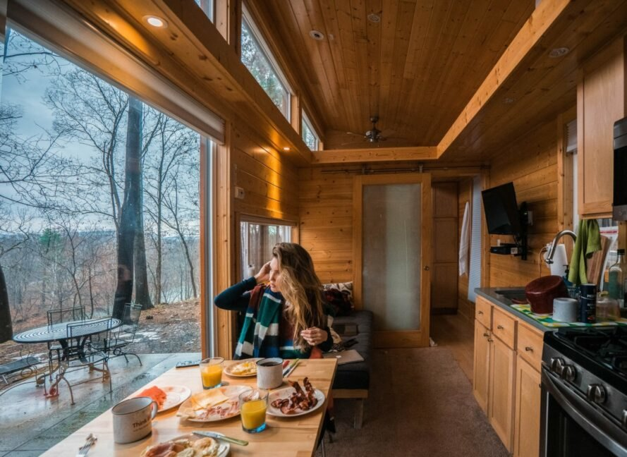 woman eating breakfast inside a tiny home with a large window