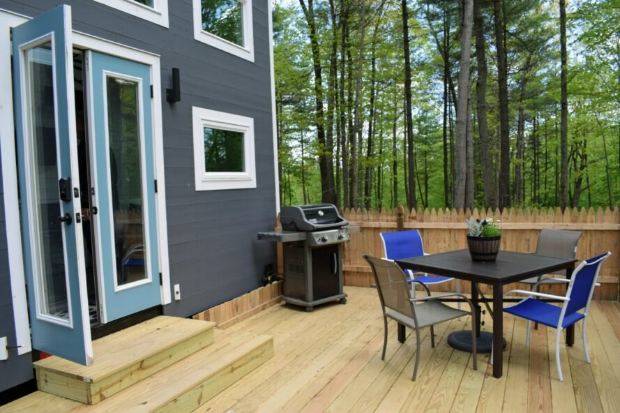grey tiny home with large deck with bbq