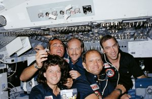 Four male astronauts and one woman astronaut crowded together in shuttle control cabin.