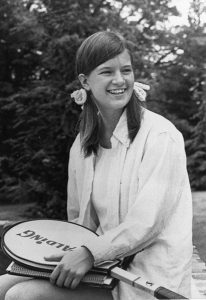 Black and white photo of smiling, seated, long-haired young woman holding a tennis racket.