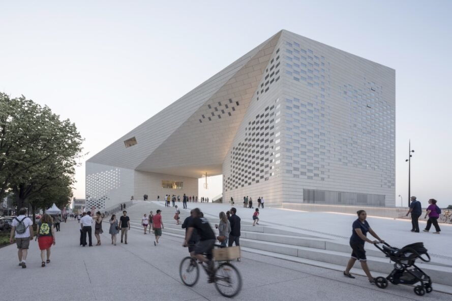 people walking or cycling past large white building