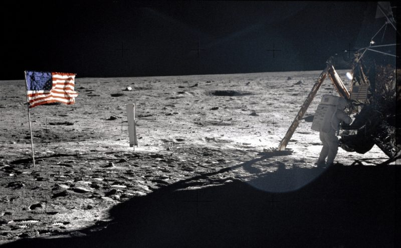 US flag, astronaut near bent leg of Apollo 11 lunar lander. Lander's shadow on the gray lunar surface. Black sky.