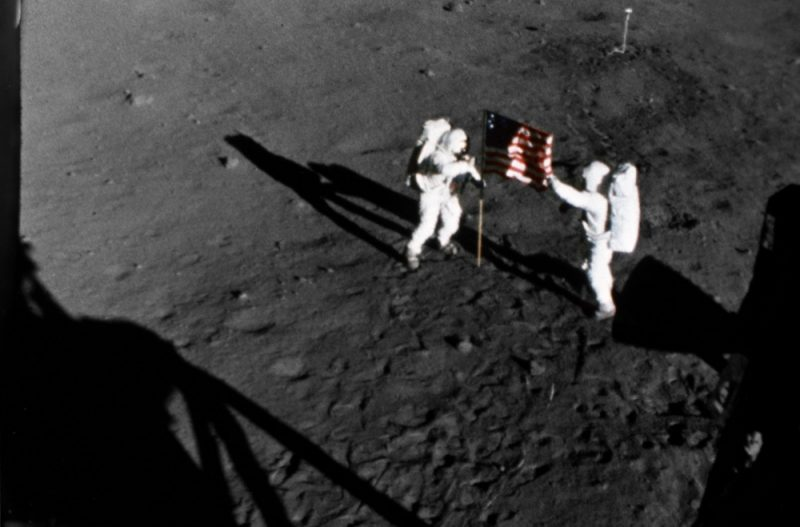 View from above of 2 astronauts in spacesuits deploying a US flag on the moon.