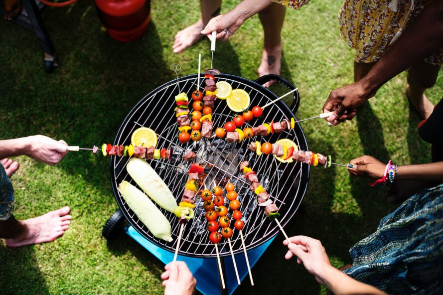 several people grilling food skewers on a grill