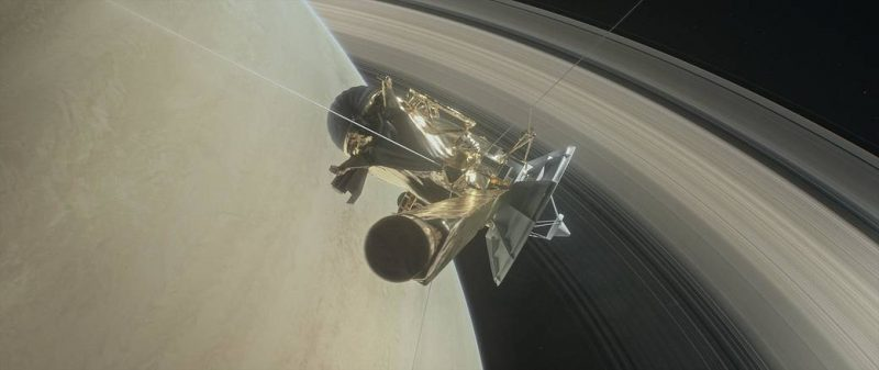 Complex spacecraft with large dish antenna against background of planet and rings.