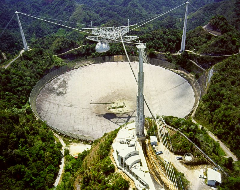 Giant white in-ground parabolic dish with receiver hung from cables above its center.