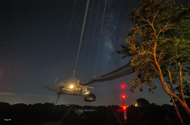 Night sky behind Arecibo radio telescope steering mechanism, lighted machinery at end of long beam.